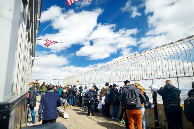 NEW YORK - MAART 16, 2015: Toeristen die van adembenemende meningen van het observatiedek genieten van Empire State Building stock afbeeldingen