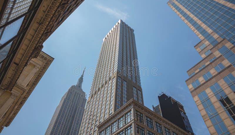 New York Manhattan Höga byggnader beskådar underifrån mot bakgrund för blå himmel royaltyfri bild