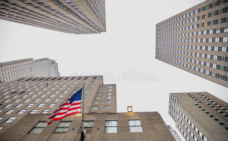 New York, Manhattan. High buildings view from below against blue sky background. New York, Manhattan commercial center. Skyscrapers perspective view and us flag royalty free stock image