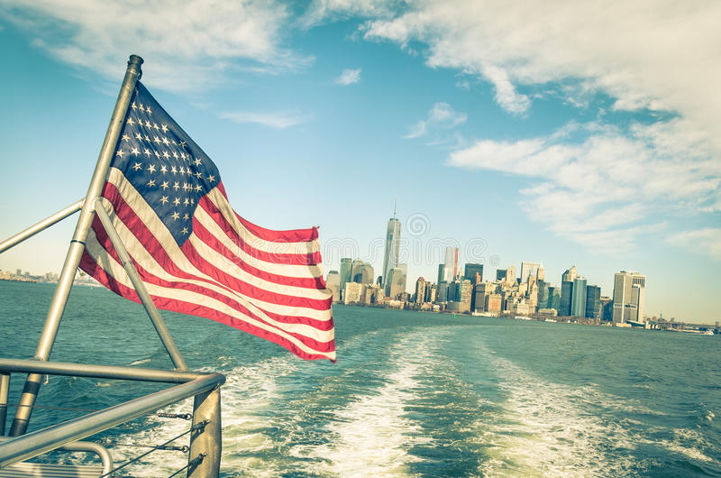New York and Manhattan skyline and American Flag. New York and Manhattan skyline from Hudson river with American Flag - Vintage filtered look with tilted horizon stock photos
