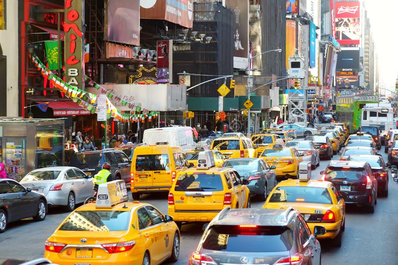 NEW YORK - MARCH 16, 2015: Yellow taxi cabs and people rushing on busy streets of downtown Manhattan. Taxicabs with their distinctive yellow paint are a widely royalty free stock image