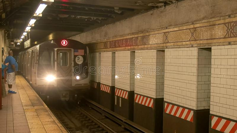 NEW YORK, NEW YORK, USA - SEPTEMBER 15, 2015: a train arrives at dekalb ave station in the subway system in ny. NEW YORK, NEW YORK, USA - SEPTEMBER 15, 2015: a stock photo