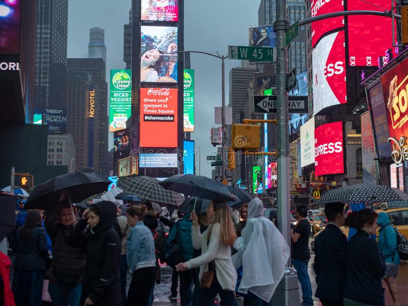 Tourists exploring Times Square while dodging rain. NEW YORK, NY – MAY 16, 2018: Tourists exploring Times Square while dodging rain royalty free stock photo
