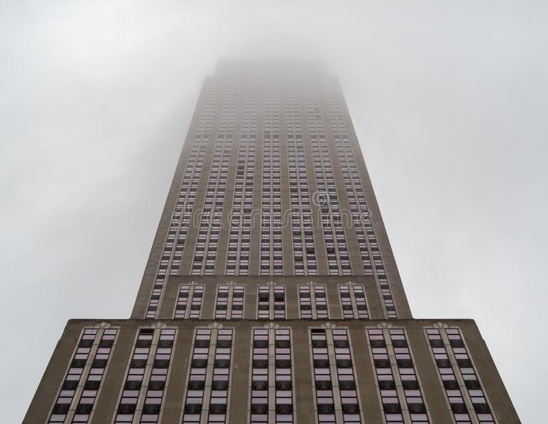Upward view of Empire State Building stretching high above fog a royalty free stock photo
