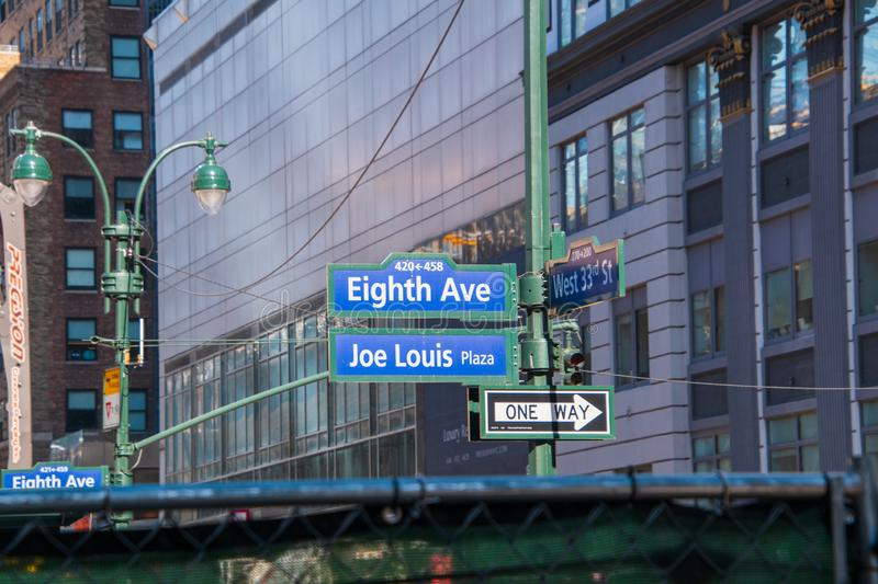 Street signs on a pole in New York City. Eight Avenue and 33rd street. Joe Lewis Plaza. New York, NY - April 3, 2019: Street signs on a pole in New York City royalty free stock photo