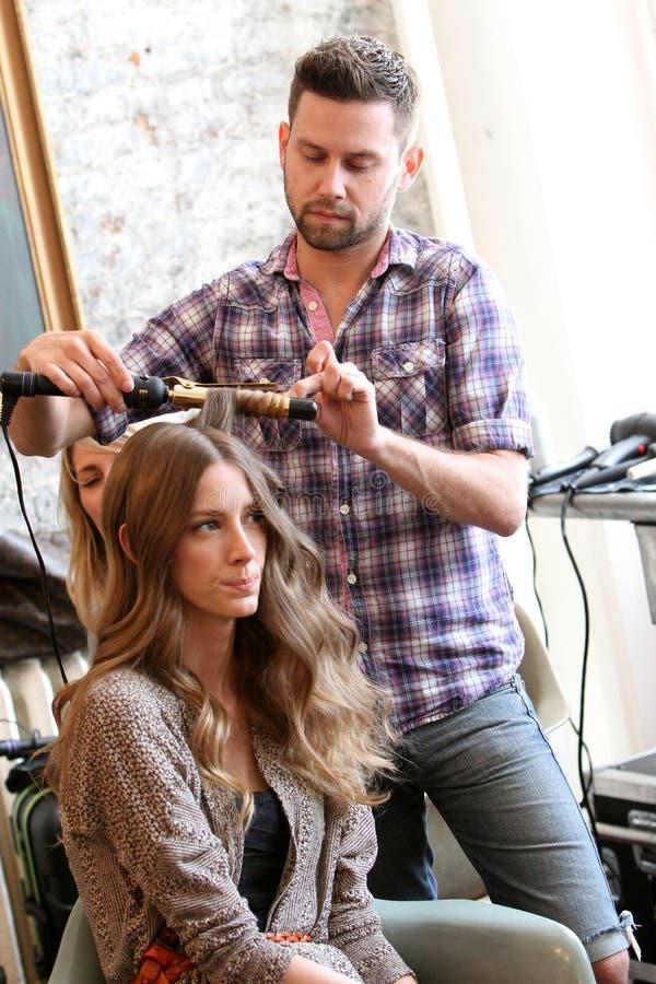 NEW YORK NY - Juni 16: En hårstylist som får modell klart i kulisserna royaltyfria foton