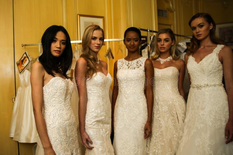 NEW YORK, NY - OCTOBER 09: Models posing backstage wearing Oleg Cassini Fall 2015 Bridal collection stock photo