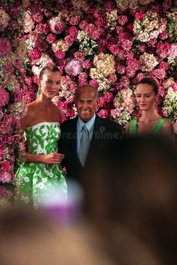 NEW YORK NY - SEPTEMBER 09: Formgivaren Oscar de la Renta (C) och modellen Karlie Kloss (v) går landningsbanan arkivfoton