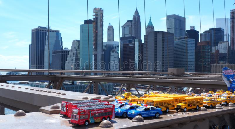 New York, NY, USA. Skyline of Manhattan skyscrapers from the Brooklyn Bridge. Toys for sale police car, school bus, yellow taxi royalty free stock photos