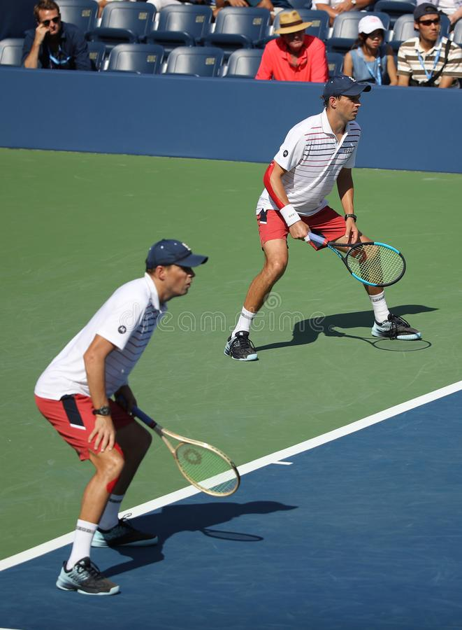 Grand Slam champions Mike and Bob Bryan of United states in action during US Open 2017 round 3 men`s doubles match. NEW YORK -SEPTEMBER 4, 2017: Grand Slam stock photography
