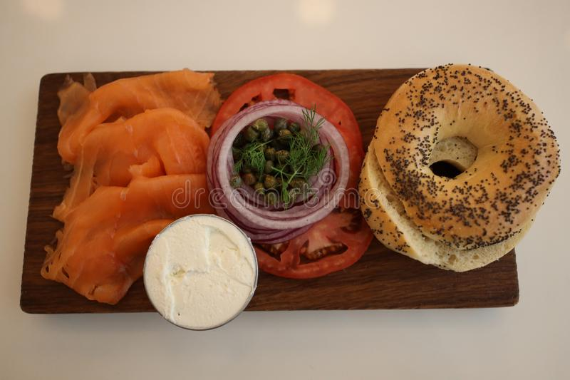 New York Style Bagel with smoked salmon with cream cheese, tomato, onion and capers. New York Style Bagel with smoked salmon with cream cheese, tomato, onion and stock photography