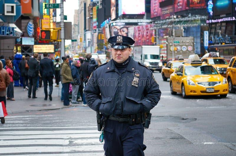 NEW YORK TIMES-QUADRAT, OKT 25, 2013: New- Yorkpolizei Deparmen-Polizeimann in der schwarzen Uniform gehend auf die Straße mit Le lizenzfreies stockbild