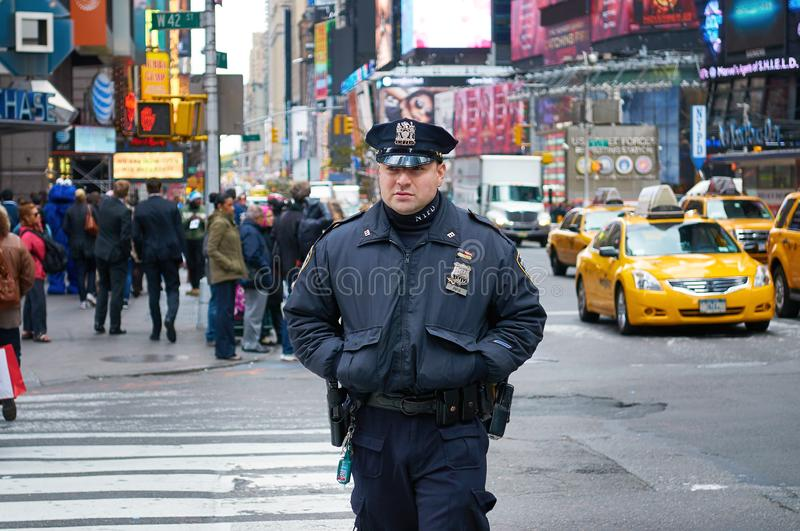 NEW YORK TIMES SQUARE, OCT. 25, 2013: New York Police Deparment police man in black uniform walking on the street with people and. Cars in the background. NYPD royalty free stock image