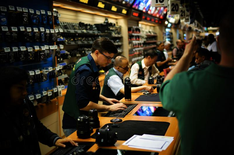 Sellers are behind the counter, one seller is typing something on keyboard, while people shop at Manhattan`s B&H Photo Video store stock image