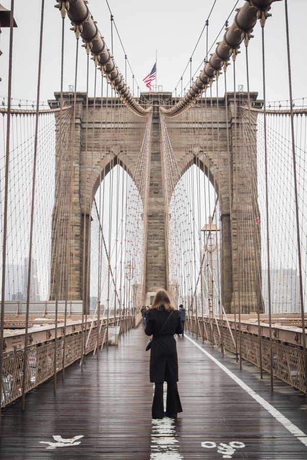 NEW YORK, USA - 24. FEBRUAR 2018: Touristisch, eine Pause machend, um die berühmte Brooklyn-Brücke in Richtung zu im Stadtzentrum stockbilder
