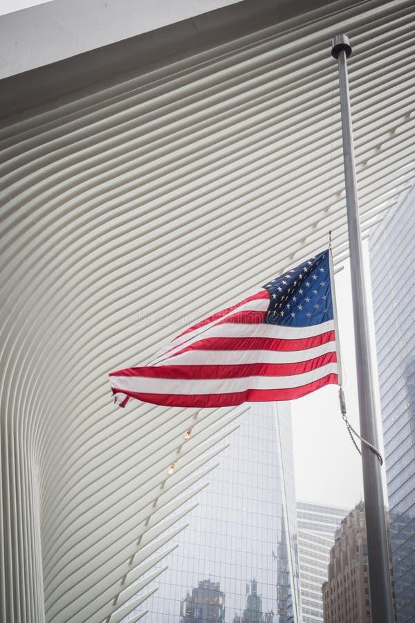 NEW YORK USA - FEBRUARI 23, 2018: Amerikanska flaggan som svävar under en arkitektonisk vinge av Oculusen på mitten av Wall Stree royaltyfria bilder