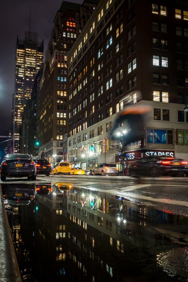 NEW YORK USA - FEBRUARI 22, 2018: Cyklistridning på natten i gatorna av New York i regnet royaltyfria foton