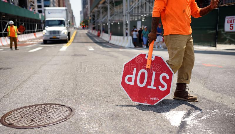 New York, USA - July 9, 2019: Black road worker carries a Stop sign down a new York city street. He stops the movement during stock photos