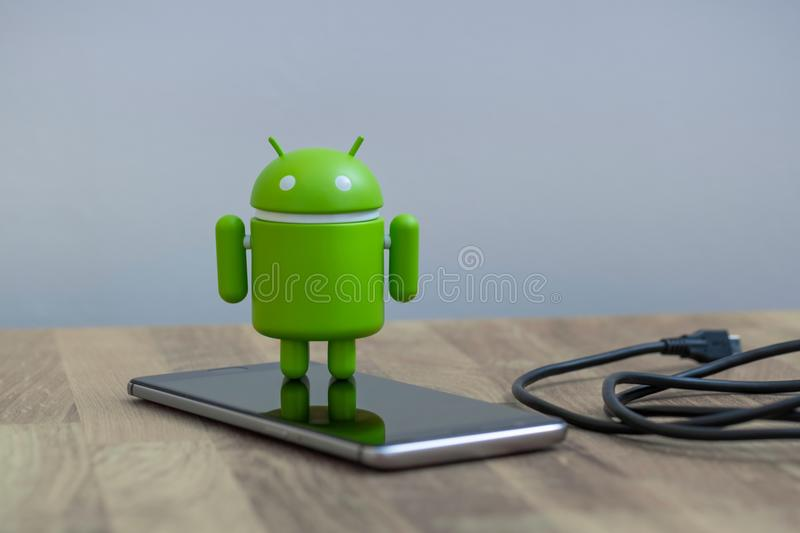 Google Android figure standing on a smart phone royalty free stock images