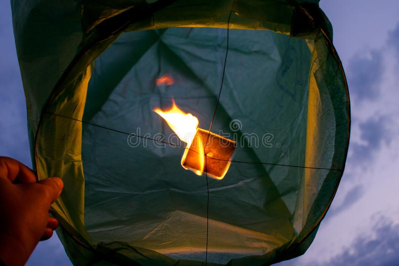 Lantern ready for launch on a summer evening. The heat emanating from the flame will lift the lamp. Photo taken under the lamppost royalty free stock images