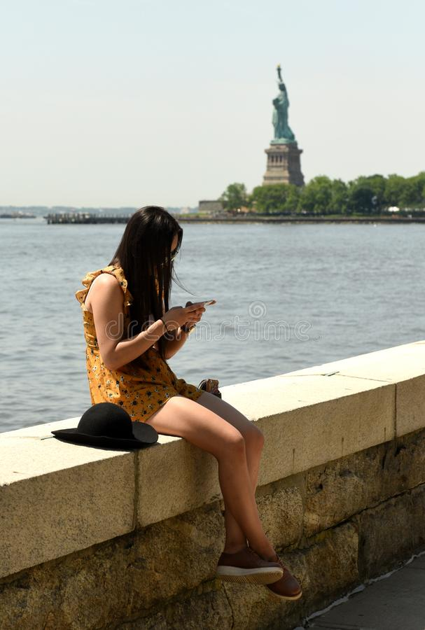 New York, USA - June 09, 2018: The girl use a smartphone at the. Ellis Island with the Statue of Liberty on the background royalty free stock images