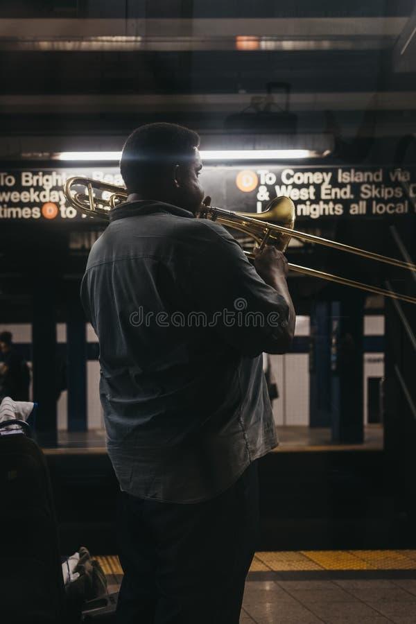 Man playing musical instrument at subway station platform in Ne. New York, USA - June 2, 2018: Man playing musical instrument at subway station platform in New royalty free stock image