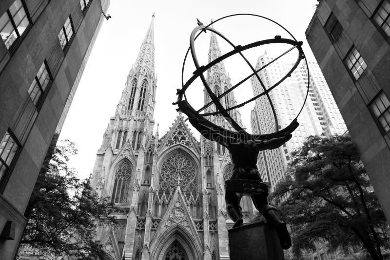 New York, USA - 8. Juni 2018: Die Statue des Atlasses in Rockefeller-Mitte steht herüber von St- Patrick` s Kathedrale lizenzfreie stockfotografie