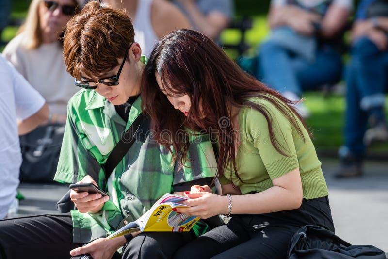 New York, USA - 21. Juni 2019: Ein paar Knaben sitzen in einem Park auf einer Bank und suchen nach Touristeninformation in einem  lizenzfreie stockfotografie