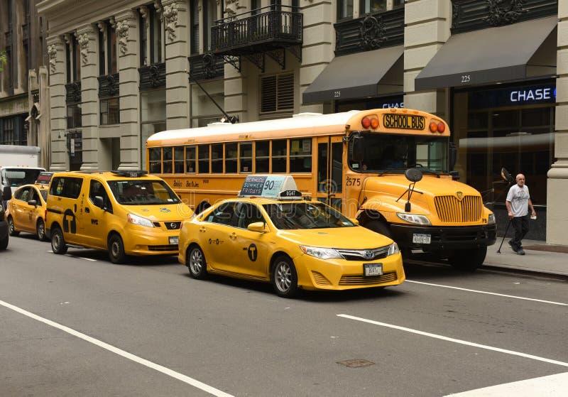 New York USA - Maj 30, 2018: Gul taxi och skolbuss på stre royaltyfri foto