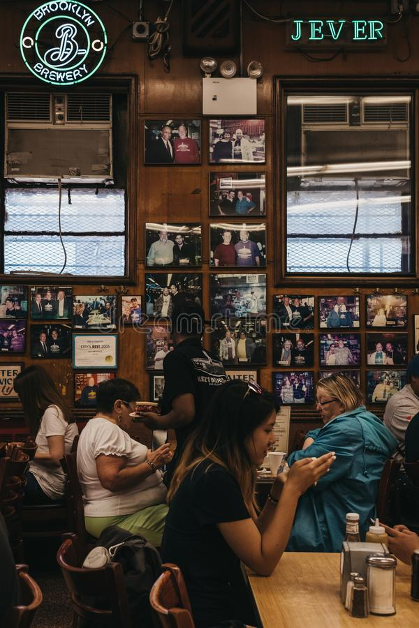 Customers sitting at the tables, eating inside Katz`s Deli in Ne stock photo
