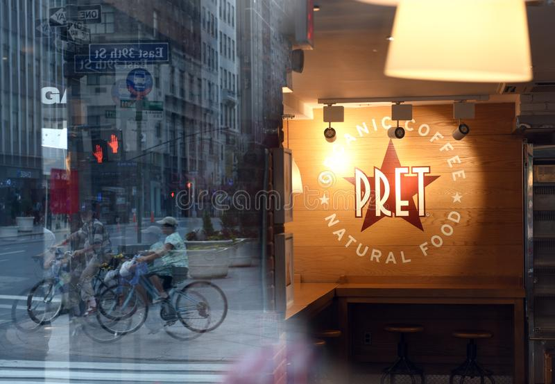 New York, USA - May 26, 2018: Fast casual restaurant Pret A Manger logo with reflection the street of New York. stock photography