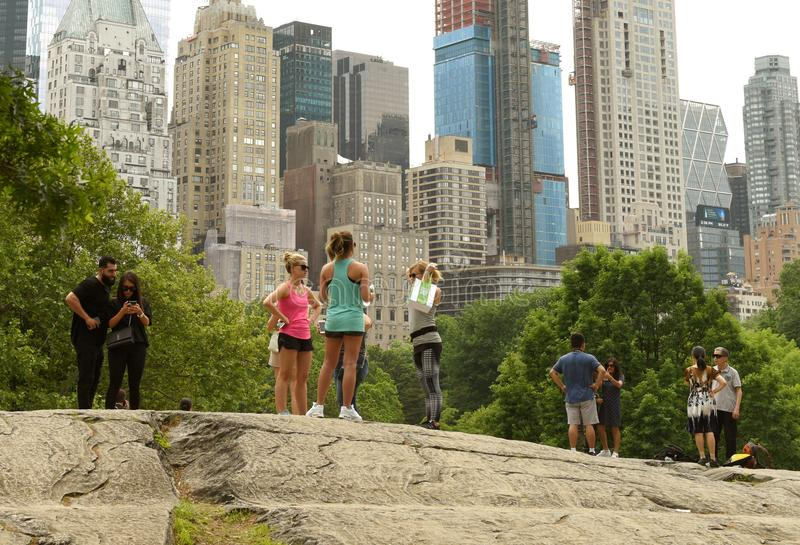 New York, USA - May 26, 2018: People in Central Park and skyscrapers of the Manhattan at the background. stock photography