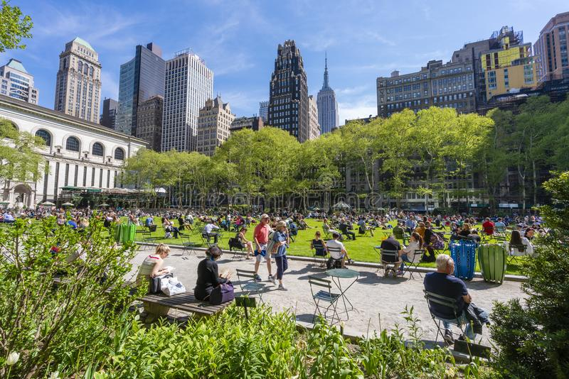 People relaxing at Bryant Park in Midtown Manhattan. New York, USA - May 10, 2018: People relaxing at Bryant Park in Midtown Manhattan stock image