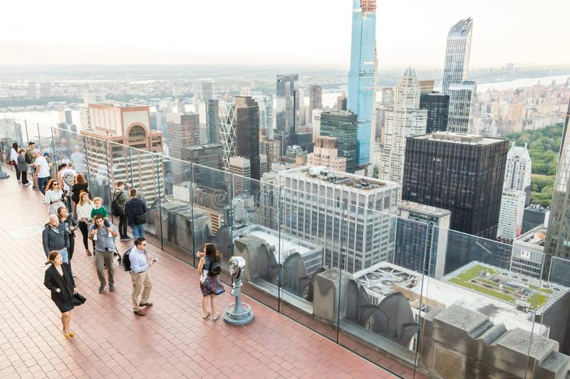 NEW YORK, USA - 17 MAY, 2019: Tourists taking pictures from rooftop on Manhattan skyscraper. NEW YORK, USA - 17 MAY, 2019: Tourists taking pictures from a stock photography