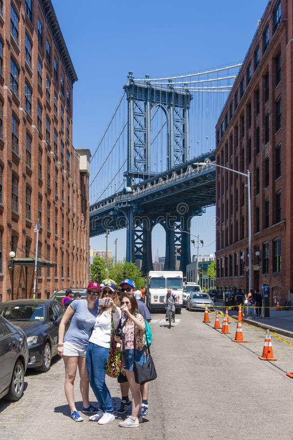 Tourists visiting Dumbo in Brooklyn. New York, USA - May 9, 2018: Tourists visiting Dumbo in Brooklyn. It is a major attraction in New York with view of stock photo