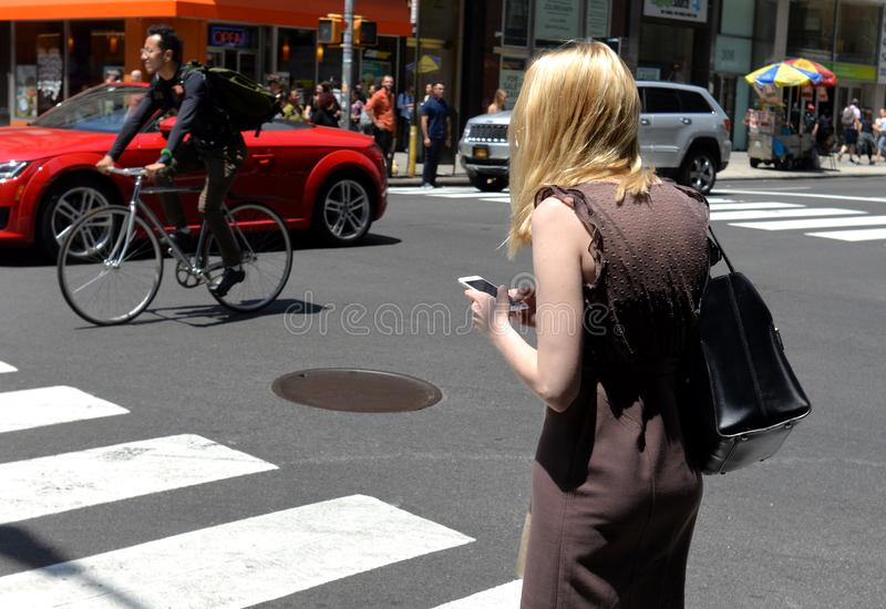 New York, USA - May 30, 2018: Woman use his smartphone at the st stock photography