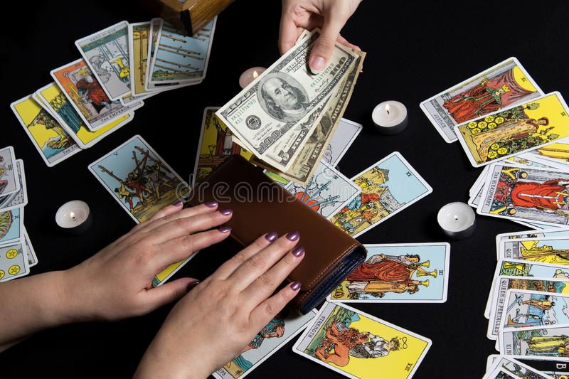 New York, USA. November 22.19. Hands holding cash dollar on background of wallet and Tarot cards. Payment for esoteric, magical. And witchcraft services in USA royalty free stock photography