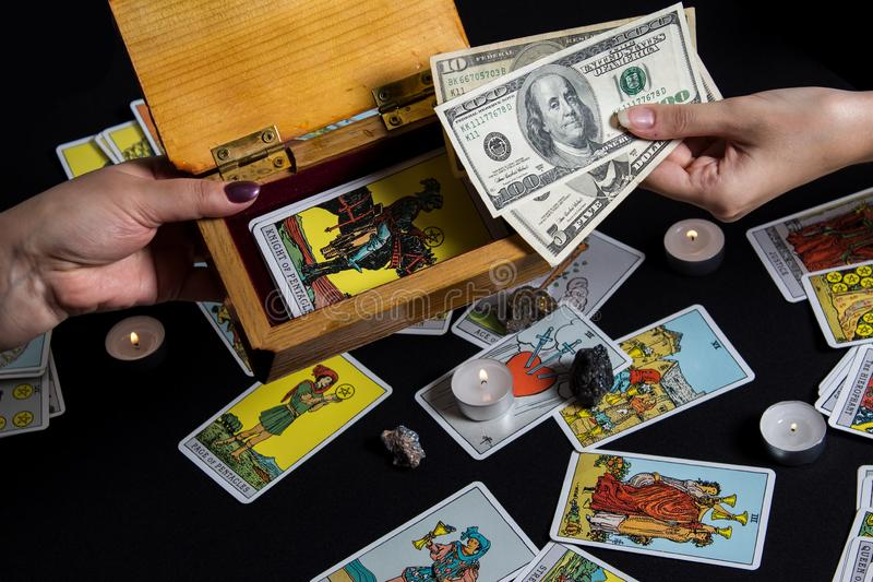 New York, USA. November 22.19. Hands holding cash dollar on background of wallet and Tarot cards. Payment for esoteric, magical. And witchcraft services in USA stock photography