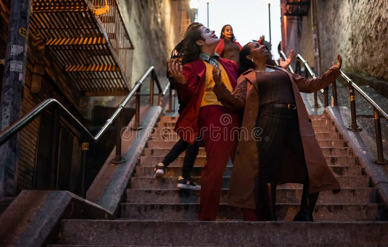 NEW YORK, USA,-NOVEMBER 31,2019: The tourist attraction staircase in Bronx, with a man impersonating the joker and a random woman royalty free stock photography