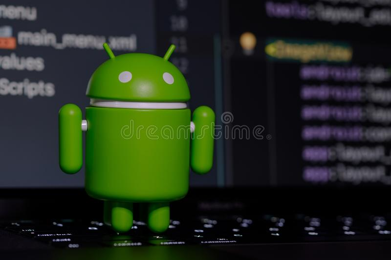 Google Android figure standing on laptop keyboard royalty free stock photography