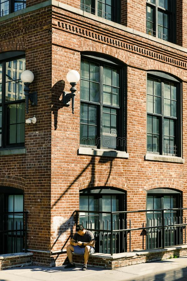 Street scene in Dumbo, Brooklyn. NEW YORK, USA - Sep 22, 2017: Street scene in Dumbo, Brooklyn. A young man with a mobile phone sits on the parapet of a brick royalty free stock photos