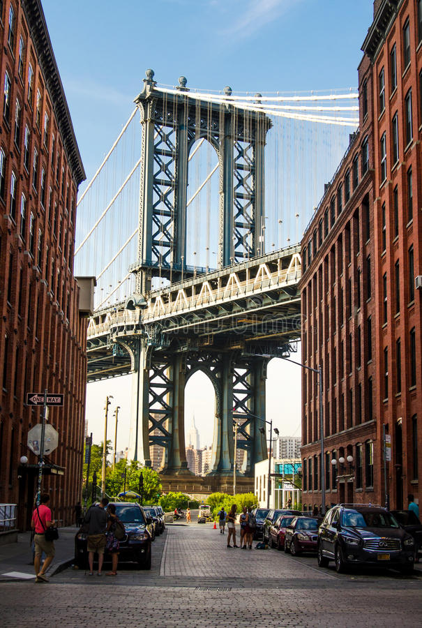 NEW YORK, USA - September 8, 2016: Manhattan Bridge from an busy. Alley in Brooklyn, New York, vertical view stock photo