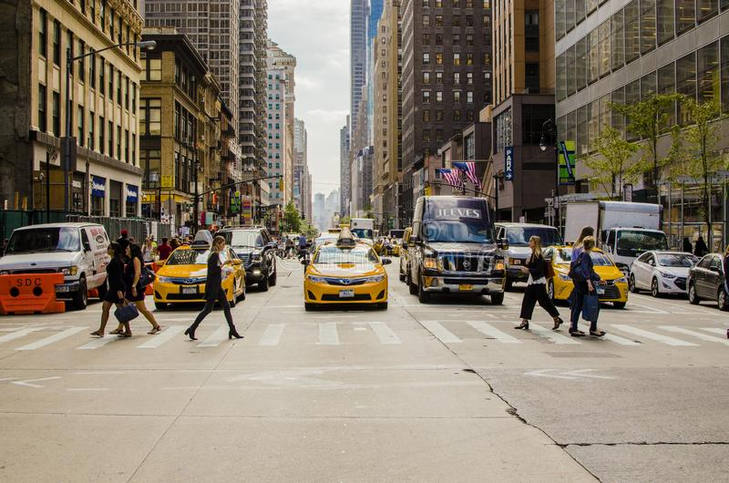 NEW YORK, NY, USA - SEPTEMBER 2017: Manhattan street with yellow taxi crossing the road royalty free stock photography