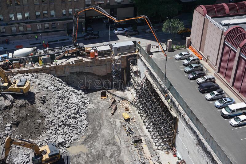 New York, New York: Workers use a cement mixer with a long arm to construct a retaining wall royalty free stock images