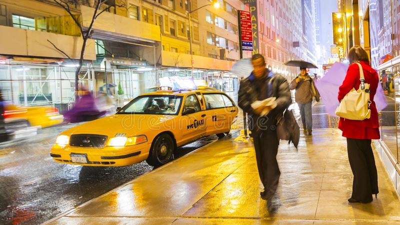 New York yellow taxi cab picking up people whilst it is raining royalty free stock images