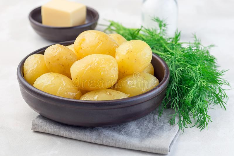 New young boiled potato topped with melted butter in ceramic bowl,   dill on a background, horizontal. New young boiled potato topped with melted butter in stock images