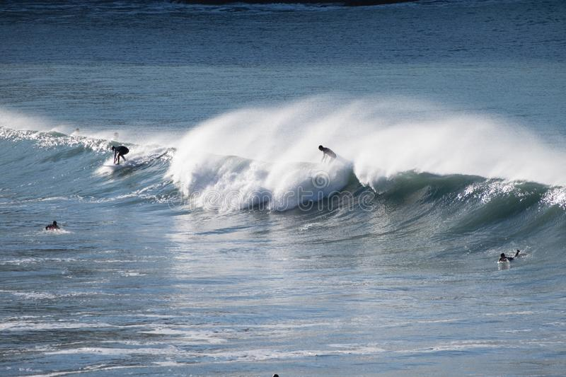 Surfers surfing on huge ocean waves in New Zealand stock photography
