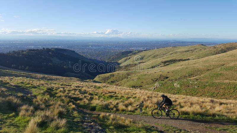 NEW ZEALAND, CHRISTCHURCH - OCTOBER 2016: A pair of unidentified couple mountain biking across Victoria hills of Christchurch New stock photo
