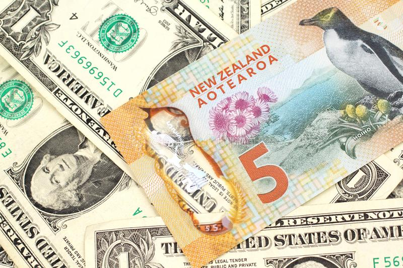 A New Zealand dollar bank note with United States one dollar bills. A close up image of a New Zealand five dollar bill with United States one dollar bills in stock photography