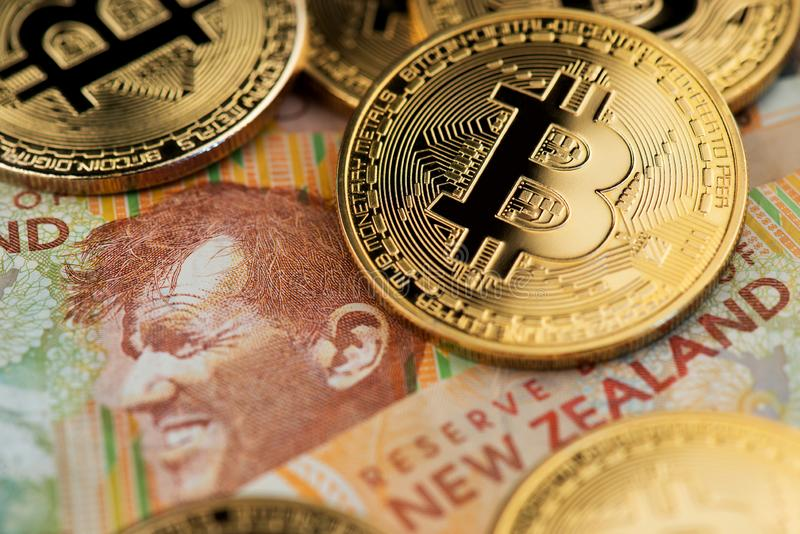 New Zealand Dollar bill with Bitcoin BTC Cryptocurrency coins. Golden Bitcoin BTC Cryptocurrency coins on New Zealand Dollar curreny banknotes stock images